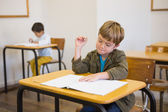 Pupil writing in notepad at his desk — Stock Photo