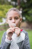 Mała dziewczynka dmuchanie mniszek lekarski — Zdjęcie stockowe