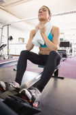 Tired young woman sitting in gym — Stock Photo