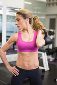 Fit woman lifting kettle bell in gym — Stock Photo