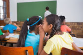 Pupils whispering in classroom — Stock Photo