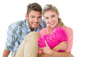 Attractive young couple sitting holding heart cushion — Stock Photo