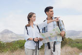 Hiking couple with map pointing ahead on mountain terrain — Stock Photo