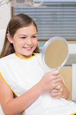 Girl holding mirror in dentists chair — Stock Photo