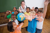 Pupils around a globe in classroom with teacher — Stock Photo