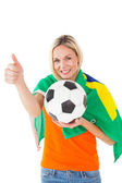 Football fan holding ball and wearing brazil flag — Stockfoto