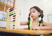 Cute pupil using abacus in classroom — Stock Photo