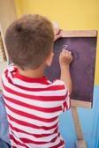 Little boy drawing on chalkboard — Stock Photo