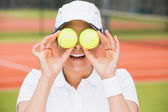 Pretty tennis player holding balls over her eyes — Stock Photo