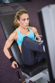 Fit young woman doing leg presses in gym — Stock Photo