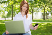 Redhead using her laptop in the park — Stock Photo