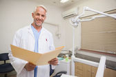 Dentist smiling at camera holding folder — Stock Photo