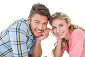 Attractive young couple lying and smiling at camera — Stock Photo