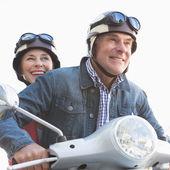 Happy senior couple riding a moped  — Foto de Stock