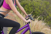 Side view of athletic woman mountain biking — Stock Photo