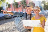 Happy tourist couple using map in the city — Stock Photo