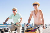 Happy casual couple going for a bike ride on the pier — Stock Photo
