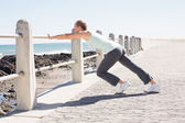 Fit mature woman warming up on the pier — Stock Photo