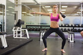Full length of woman lifting kettle bell in gym — Stock Photo