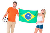 Excited football fan couple holding brazil flag — Stock Photo