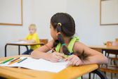 Pupils colouring at desks in classroom — Stock Photo
