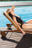 Beautiful woman in bikini relaxing by swimming pool — Foto de Stock