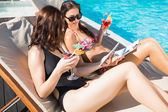 Women holding drinks by swimming pool — Stock Photo