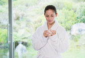 Beautiful woman in bathrobe having tea — Stock Photo