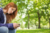 Redhead relaxing in the park sending a text — Foto Stock