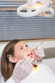 Dentist using mouth retractor on girl — Stock Photo