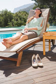 Beautiful woman relaxing on sun lounger by swimming pool — Stock Photo