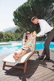 Waiter serving woman breakfast by swimming pool — Stock Photo