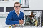 Smiling technician working on broken computer — Stock Photo