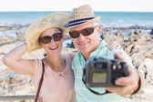 Happy casual couple taking a selfie by the coast — Foto Stock
