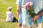 Senior man hiding flowers behind his back — Stock Photo