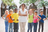 Teacher standing with pupils in courtyard — Stock Photo