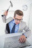 Angry businessman holding hammer over laptop — Stock Photo