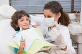 Pediatric dentist showing little boy in chair the toothrbrush — Stock Photo