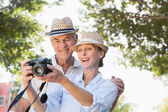 Happy senior couple looking at their camera — Stockfoto