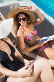 Women reading books on sun loungers by swimming pool — Stock fotografie