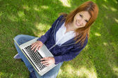 Pretty redhead in the park using laptop — Stock Photo