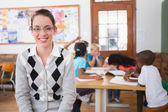 Teacher smiling at top of classroom — Stock Photo