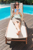 Woman reading book on sun lounger by pool — Stock Photo