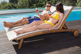 Couple with drinks sitting by swimming pool — Stock Photo