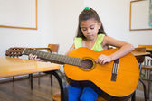 Pupil playing guitar in classroom — Stock Photo