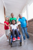 Disabled pupil in hall with her friends — Stock Photo