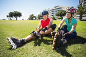 Fit mature couple tying up their roller blades on the grass — Stockfoto