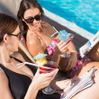 Women with drinks by swimming pool — Stock Photo #51600141