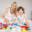 Mother and daughter playing with building blocks on bed — Stock Photo #51600867