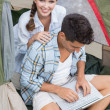 Couple using laptop in tent — Stock Photo